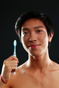 Portrait of a young man with toothbrush on black background