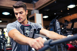Portrait of a young man workout on fitness machine at gym