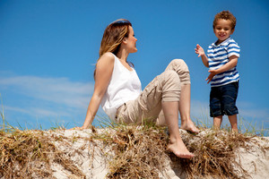 Portrait of a young mom looking at her charming son against the bright sky