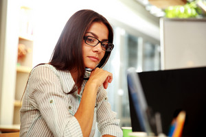 Portrait of a young pensive businesswoman in glasses at office