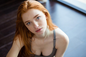 Portrait of a young redhead woman sitting on the floor and looking at camera