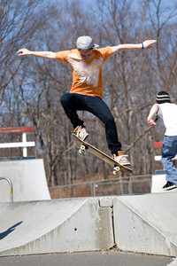 Portrait of a young skateboarder performing a jump at the skate park.