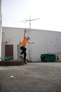 Portrait of a young skateboarder performing a trick in an urban setting.