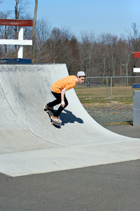 Portrait of a young skateboarder skating on a ramp at the skate park.