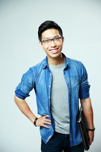Portrait of a young smiling asian man holding laptop on gray background