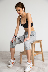 Portrait of a young sports woman sitting on the chair at gym