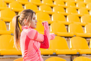 Portrait of a young sports woman stretching hands at stadium