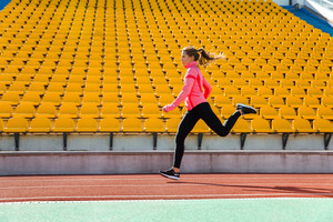 Portrait of a young woman running at stadium