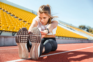 Portrait of a young woman stretching on the floor at stadium