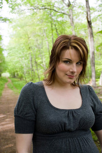 Portrait of a young woman walking on a path through the woods.