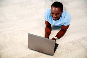 Portrait of african man lying on the floor and using laptop