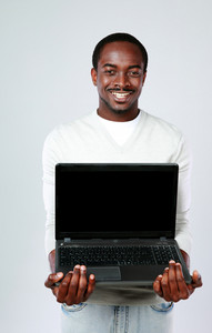 Portrait of african man showing blank laptop screen on gray background