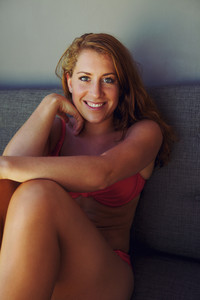 Portrait of an attractive young woman wearing red bikini sitting on a couch smiling at camera.