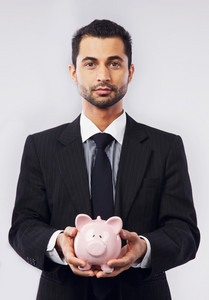Portrait of an executive holding a piggy bank