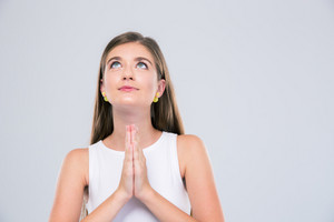 Portrait of attractive female teenager praying