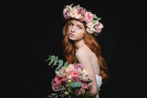 Portrait of attractive redhead woman posing with flowers over black background