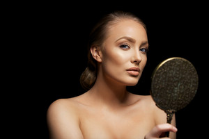 Portrait of attractive young female model holding a hand mirror looking at camera. Sexy young woman against black background.