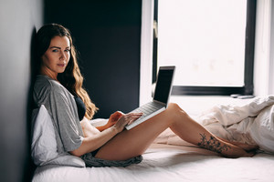 Portrait of attractive young lady sitting on bed with a laptop. Caucasian female model in lingerie working on laptop in bedroom.
