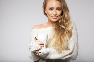 Portrait of attractive young wearing sweater holding a hot cup of coffee. Caucasian female fashion model on grey background with copyspace.