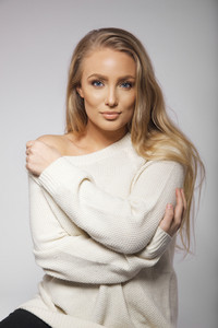 Portrait of attractive young woman wearing oversized sweater. Caucasian young female model posing against grey background.