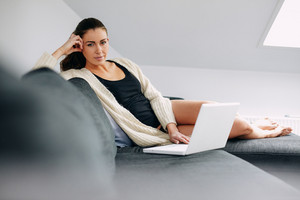 Portrait of attractive young woman with a laptop sitting on a couch looking at camera. Relaxed female model working on laptop at home.