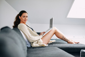 Portrait of beautiful young woman sitting on a couch with a laptop looking at camera. Caucasian female model indoors on sofa using laptop.