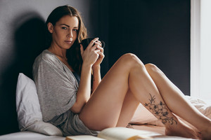 Portrait of beautiful young woman sitting on her bed holding a cup of coffee looking at camera.
