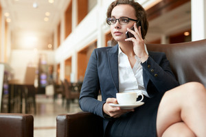 Portrait of businesswoman sitting at coffee shop using mobile phone. Female executive with cup of coffee talking on cell phone.