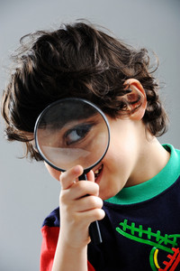 Portrait of child looking closely with magnifying glass