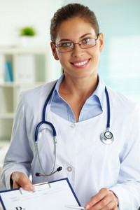 Portrait of confident female doctor with clipboard looking at camera