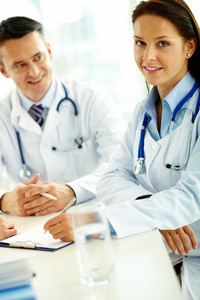 Portrait of confident female doctor with stethoscope looking at camera at workplace