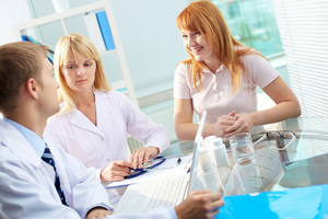 Portrait of confident practitioners consulting and their patient looking at them in hospital