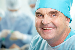 Portrait of confident senior surgeon looking at camera on background of working group