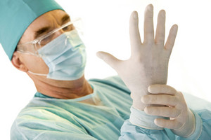 Portrait of doctor dressing medical gloves after operation