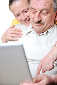 Portrait of elderly man and woman working on laptop