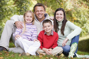 Portrait of family sitting amongst autumn trees