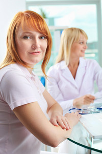 Portrait of female patient looking at camera with doctor on background
