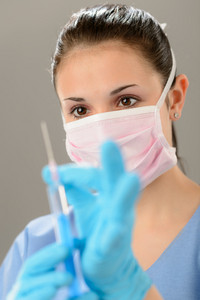 Portrait of female physician holding syringe wearing mask
