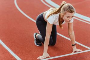 Portrait of female runner standing in start position at stadium