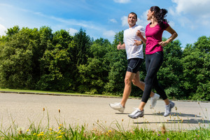 Portrait of fit Caucasian couple running outdoors