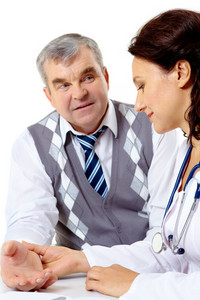 Portrait of friendly therapist checking patient pulse during medical consultation