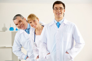 Portrait of friendly therapists standing in line and looking at camera with happy clinician in front