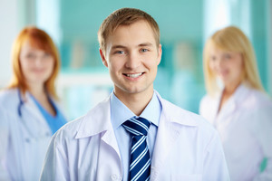 Portrait of handsome doctor in white coat looking at camera