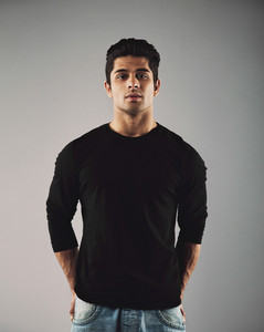 Portrait of handsome young hispanic guy posing. Smart male fashion model posing on grey background.