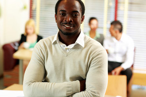 Portrait of happy african businessman standing in front of colleagues at office