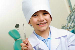Portrait of happy boy in medical uniform holding dentistry tools in hand