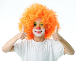 Portrait of happy funny clown kid with thumbs up