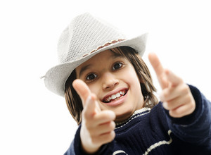Portrait of happy joyful stylish little boy with hat pointing fingers at you