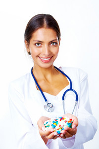 Portrait of happy pharmacist with handful of vitamins looking at camera