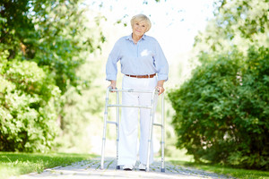 Portrait of happy senior patient walking in the park in summer